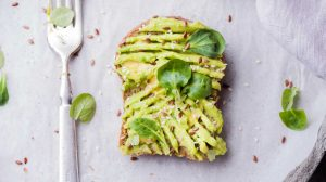 nM1FZ-SCXnE-wheat bread with avocado spread beside white plastic spoon-easy vegan recipes-us-feature