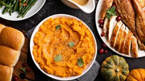 Mashed sweet potatoes with butter and cinnamon on Thanksgiving table with turkey and green beans overhead shot | Christmas Side Dishes Every Christmas Table Needs | delicious side dish | Featured
