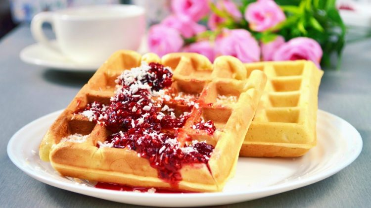 Sweet Waffles topped with Warm Raspberry Sauce and a white cup of coffee | Delicious Coconut Flour Waffles You Can Make For Quarantine | coconut flour recipes | Featured